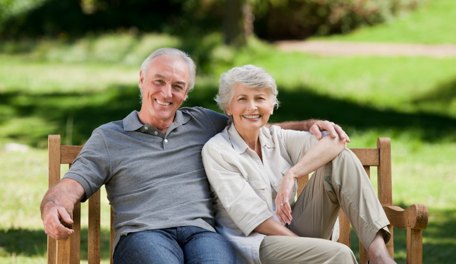 Senior couple sitting on a bench in the park